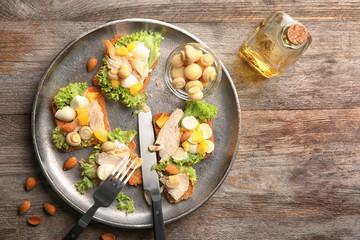 Plate with tasty chicken bruschettas on wooden table