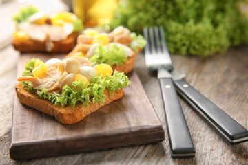 Wooden board with tasty chicken bruschetta, closeup