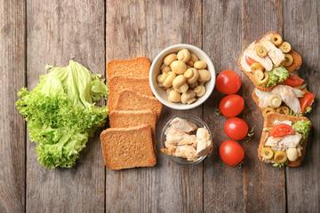 Tasty chicken bruschettas and ingredients on wooden table, flat lay