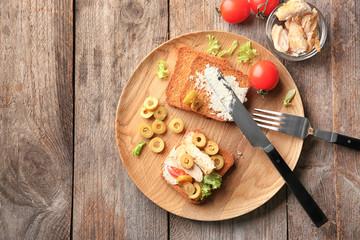 Plate with tasty chicken bruschetta on wooden table
