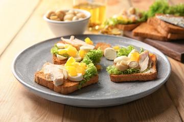 Plate with tasty chicken bruschettas on table