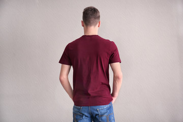 Young man in color t-shirt on light background. Mockup for design