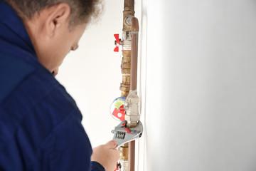 Plumber repairing pipe, indoors