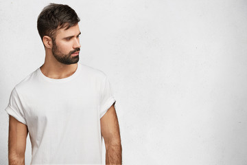 Bearded serious male in white t shirt, poses against white blank copy space for your advertisment or promotional text. Handsome man dressed casually, advertizes something, poses in studio alone