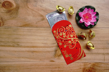 Chinese new year festival decorations ingots, red packet (ang pow), Malaysia Ringgit banknote and a pink lotus flower on wooden background with copy space.