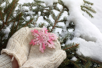 gift with a warming mood/ snowflake knitted from pink thread in warm mittens on background of winter landscape