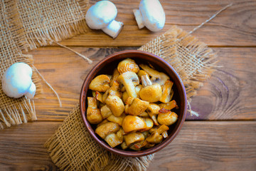 Roasted mushrooms. Homemade roasted mushrooms in a bowl on a wooden background. Vegetarian low-calorie dinner recipe. Top view