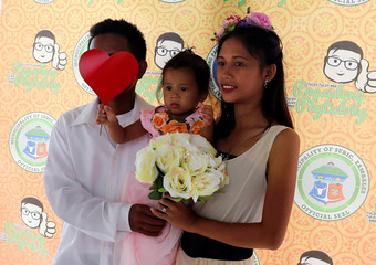 A couple with a child pose at a wedding photo booth before the start of a free mass wedding ahead of Valentine's Day celebration at Subic, Zambales