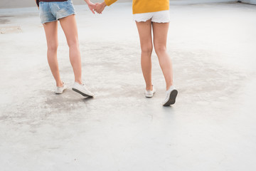 close up  foot of two woman holding hand and walking together.
