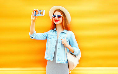 young smiling woman takes a picture self portrait on a smartphone on orange background