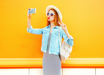 young woman takes a picture self portrait on a smartphone on orange background