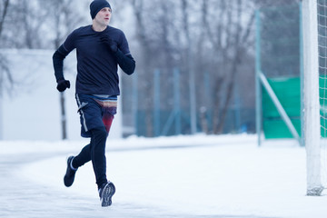 Photo of sportive man running at stadium in winter