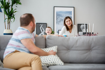 Family photo of man sitting back on couch, son and wife behind sofa