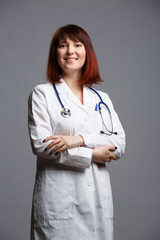 Photo of female doctor in white lab coat and with phonendoscope