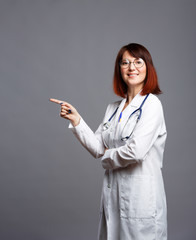 Image of smiling brunette doctor in white coat and with phonendoscope in glasses points finger at empty space