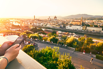 A tourist with a mobile phone on an observation deck in the square Michelangelo watching the sunset over Florence, Italy