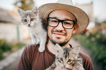 Happpy young bearded farmer holding two little kitten in hands outdoor in village with abstract background. Smiling man in glasses and straw hat playing with funny cute pets. Have fun in countryside.