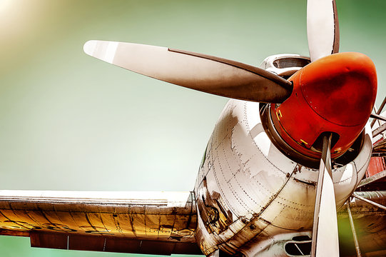 Closeup of an old airplane turboprop engine with propeller blades, parts of wings and aircraft fuselage - historic vintage plane in dramatic look retro style