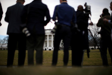 Members of the media stand on the South Lawn of the White House as they await arrival of U.S. President Donald Trump and Harley Davidson executives