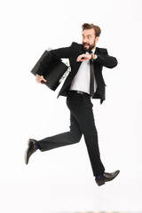 Excited young businessman with suitcase running
