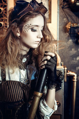 Portrait of a beautiful steampunk woman, with a telescope on a grunge gear background.