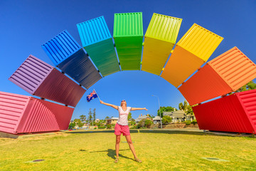 Australia travel welcome. Happy woman with Australian flag waving enjoys rainbow sea container. Fremantle Port, Perth, WA, Australia. Homosexuality and universal symbol of hope concept. Iconic place.