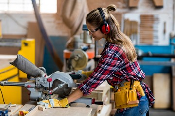 Female carpenter cutting wooden plank with electric saw
