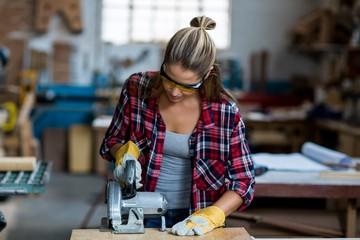 Female carpenter using a jigsaw
