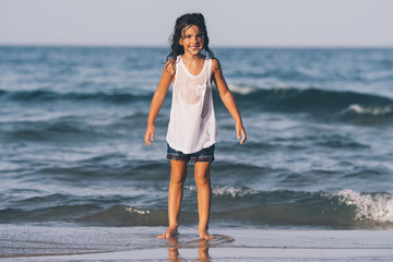 Little happy girl playing on the beach.