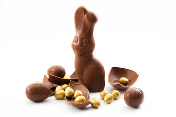 Passover, happy easter and good friday wishes concept with a chocolate bunny surrounded by pieces of chocolate eggs isolated on white background with a clipping path included
