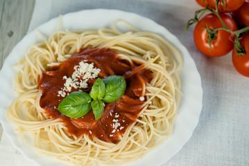 Italian pasta spaghetti topped with a tomato and fresh basil