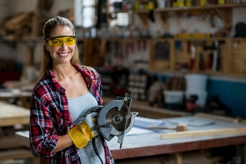 Female carpenter standing with circular saw in workshop