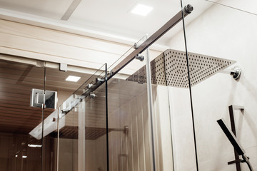 Metal structure of the upper fasteners and rollers for the sliding glass door in the shower enclosure conjugated with the glass door to the sauna view in the interior