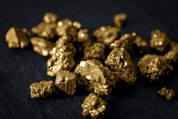 Gold mining and and investment in precious metals concept with close up on golden nuggets on a black background