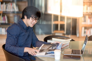Young Asian man student reading book and magazine in public library, education research and self learning in university life concepts