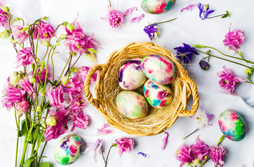 Easter eggs and colorful iris flowers on white textile