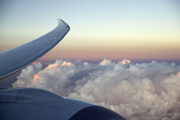 Aircraft turbo prop jet engine and wingtip in flight with sunset sky and clouds