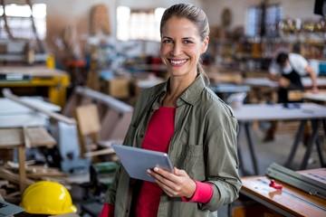 Female carpenter using digital tablet