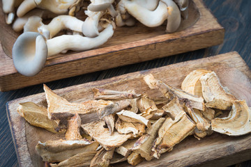 Raw and dried mushrooms in craft wooden plates