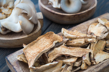 Dried mushrooms and fresh raw oyster mushrooms in craft wooden p