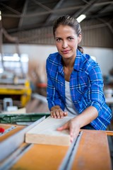Portrait of female carpenter with wooden plank