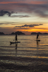 two man silhouette standing on sup boards on sunset time in El Nido, Palawan, Philippines, Corong Corong beach