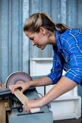 Female carpenter working with sanding machine