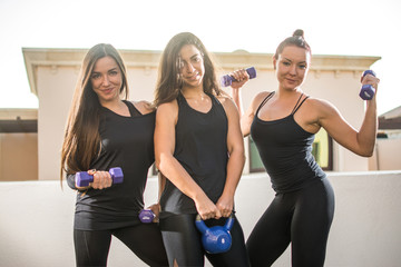Three young woman in sportswear posing with weights outdoors.