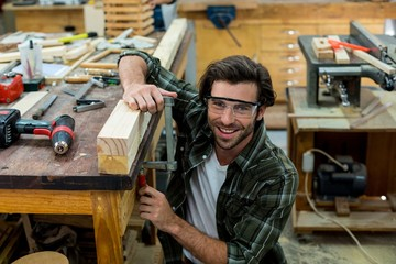 Portrait of male carpenter clamping wood