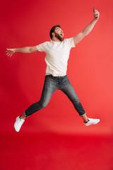 Bearded man jumping isolated using mobile phone make selfie.