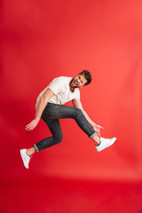 Excited bearded man jumping isolated