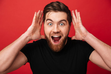 Portrait close up of excited stylish man wearing black t-shirt screaming in surprise on camera and posing with hands near face, isolated over red wall