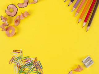 Some colored pencils of different colors and a pencil sharpener and pencil shavings on а yellow background