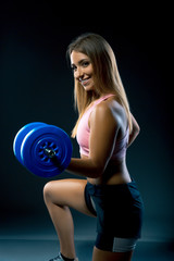 A woman with a smile on her face working out with weights, while on her knees. athlete with dumbbells trains on a dark background